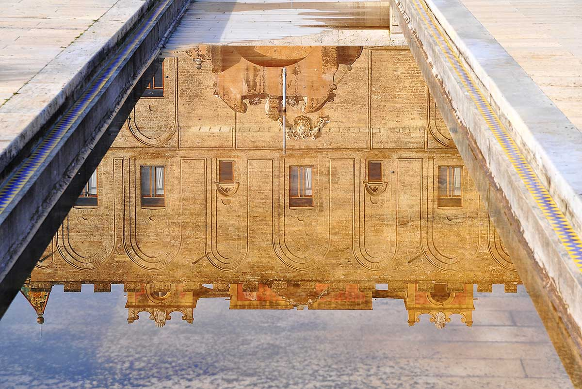 Een weerspiegeling van de gevel van het paleis in de vijver in de tuin